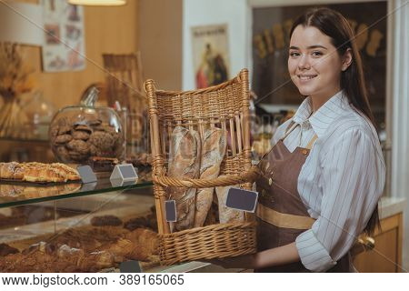 Charming Young Female Baker Wearing Apron, Holding Basket With Freshly Baked Delicious Bread. Lovely