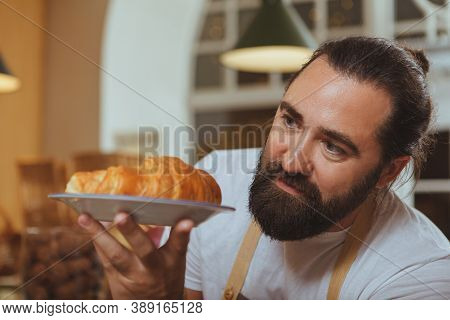 Selective Focus On Fresh Tasty Croissant On The Plate Bearded Male Baker Is Holding, Copy Space. Pro