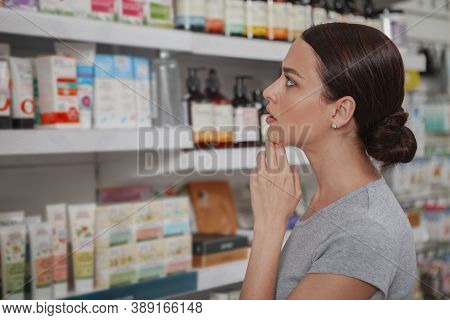 Close Up Profile Shot Of A Beautiful Young Woman Looking Thoughtfully At Drugstore Shelves With Prod