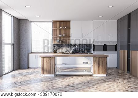 Interior Of Stylish Kitchen With Concrete Walls, Wooden Floor And White Cabinets With Built In Sink