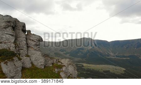 Amazing Green Valley. Enormous Grey Cliff With Huge Boulders.