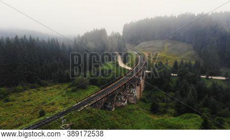 Unique Arched Viaduct Bridge In The Carpathians. Green Hills Covered With Light Haze.