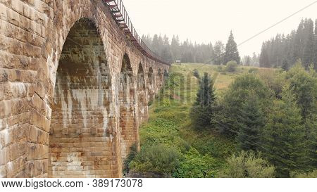 Close View Of Viaduct Arches. Railroad On The Bridge. Green Hills With Spruces On The Background.