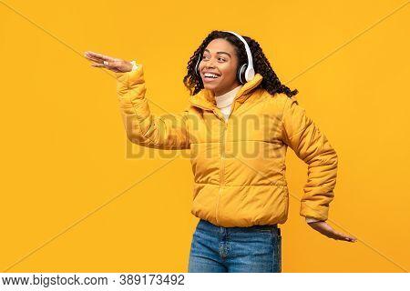 Cheerful African American Lady Listening To Music Wearing Wireless Headphones, Dancing Having Fun Po