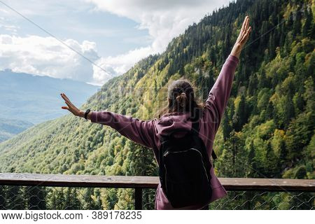 Thrilled Woman Enjoying The View Of A Mountain Slope Covered With Forest