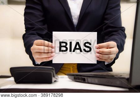 The Word Bias Is Written On A White Piece Of Paper Held By A Business Woman. Personal Opinions Preju
