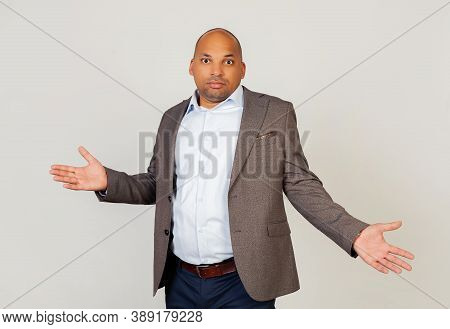 Young Male African American Businessman Looking At The Camera, Spread His Hands Guiltily. An Ignoran