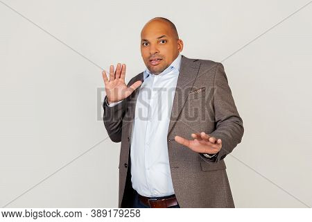 Young Male African American Businessman Screaming With A Frightened Expression On His Face, Afraid A