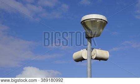 Vrouwenpolder, The Netherland - October 11, 2020: Speakers On A Damaged Lamppost Against A Partly Cl