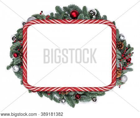 Christmas design copmosition of candy cane striped border frame noble fir tree branch baubles and red holly berries pine cones isolated on white background with copy space for text