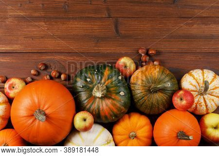 Wood background with pumpkin, apples and nuts. Copy space for text