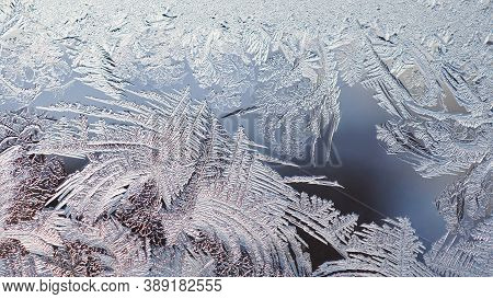 Ice And Frost On A Window Pane In Winter. The Pattern Of Crystals Looks Like A Magical Plant. Weathe