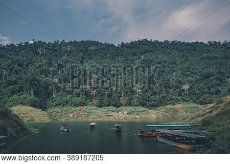 Passenger Boats For Tourism Are Parked In The River On Sunset Background At Khun Dan Prakarnchon Dam
