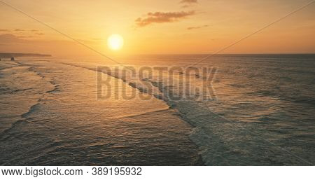 Ocean waves at sun set light aerial view. Sunset wavy seascape at tropical paradise resort of Sumba Island, Indonesia, Asia. Cinematic nobody nature scenery at soft sunlight drone shot