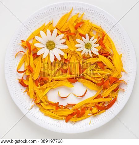 Funny Face Made From Flowers And Petals On Plate.