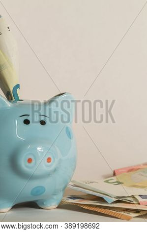 Euro Bank Note In A Piggy Bank And A Pile Of Bank Notes Beside.