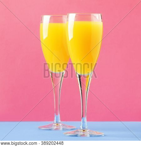 Mimosa Alcohol Cocktail With Orange Juice And Dry Champagne Or Sparkling Wine In Glasses, Blue Pink