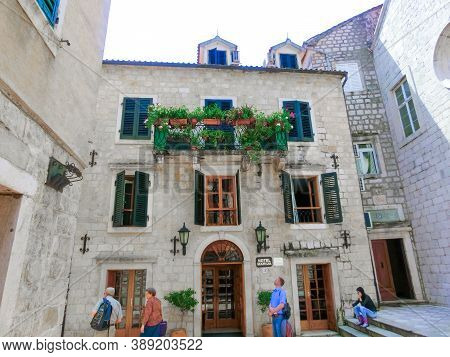 Kotor, Montenegro - May 07, 2014: People Going Near Hotel On St. Lukes Square Surrounded By Traditio