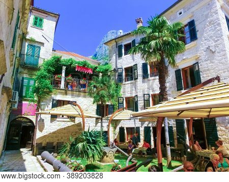 Kotor, Montenegro - May 07, 2014: People Sittiing At Cafe On St. Lukes Square Surrounded By Traditio