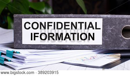 Confidential Information Is Written On A Gray File Folder Next To Documents. Business Concept