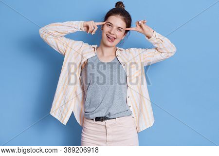 Joyful Girl Shows Tongue To Camera And Holds Fore Fingers On Temples, Showing Child's Behavior, Wear