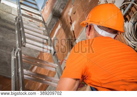 Caucasian Construction Contractor Worker In His 40s Wearing Orange Hard Hat Going Upstairs Using Alu