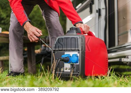 Caucasian Men In His 40s Firing Up Gas Powered Portable Inverter Generator To Connect Electricity To