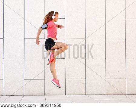 Full Body Side View Of Energetic Young Fit Female In Sportswear And Headphones With Phone Armband Ju
