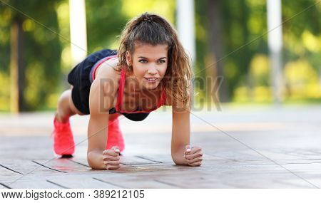 Happy Smiling Motivated Young Sporty Female Doing Forearm Plank Exercise During Abs Workout In Summe