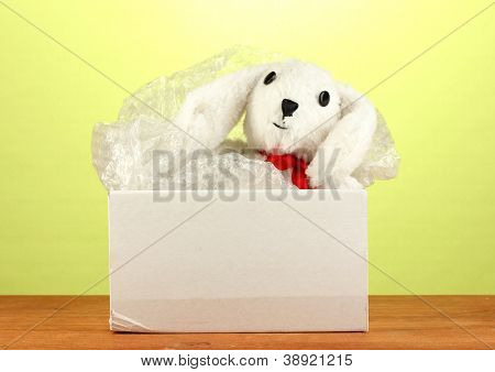 Opened parcel with a child's toy on green background close-up
