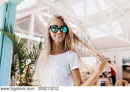 Wonderful Laughing Girl Touching Her Long Blonde Hair During Photoshoot In Cafeteria. Cheerful Femal