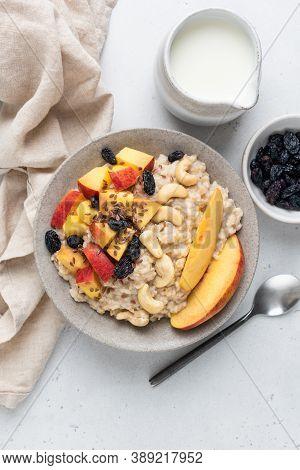 Porridge Oats With Peach, Raisins, Cashew Nuts And Linseeds. Healthy Vegan Vegetarian Breakfast Food