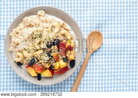 Oatmeal Porridge Bowl With Peach, Raisins And Hemp Seeds. Top View. Clean Eating, Vegan Breakfast Fo