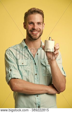 Overpowering Mens Scent. Happy Guy Hold Perfume Bottle Yellow Background. Advertising Perfume. Eau D