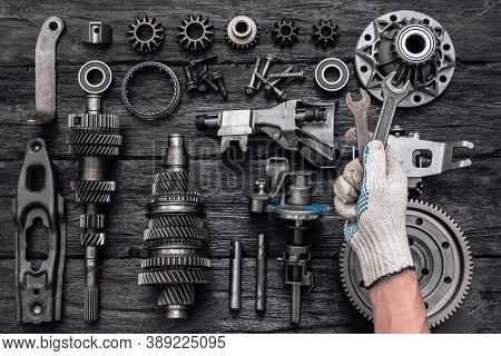 Disassembled Parts Of A Car Gearbox And An Auto Mechanic With A Wrench In Hand.