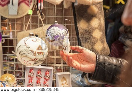 Visitor Buying Christmas Tree Decorations At The Christmas Street Market. Customer Holds Christmas T