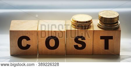 Cost Word On Wooden Cubes With Letters And Coins. Analyze Spending Or Payment, Expense Or Company Pr