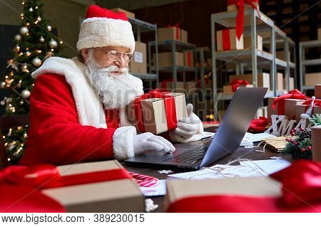 Happy Old Santa Claus Wearing Costume Holding Gift Box Using Laptop Computer Sitting At Workshop Tab
