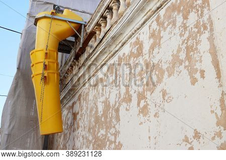 Suspended Sections Of The Yellow Garbage Chute Are Attached To The Facade Of A Historic Building Und