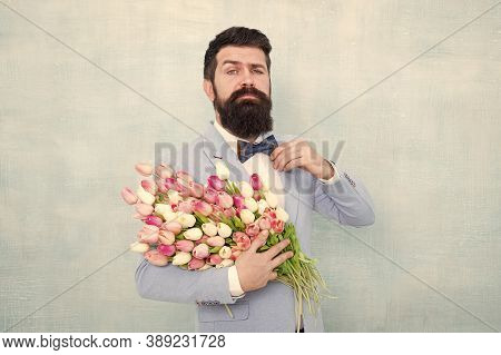 Happy Womens Day. Bearded Man Hold Spring Flowers. Tulip Bouquet For Womens Day. Hipster Wear Formal