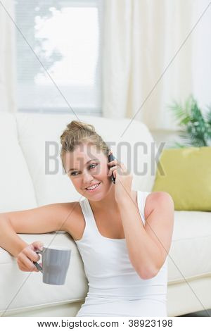 Woman using mobile phone for calling while drinking coffee