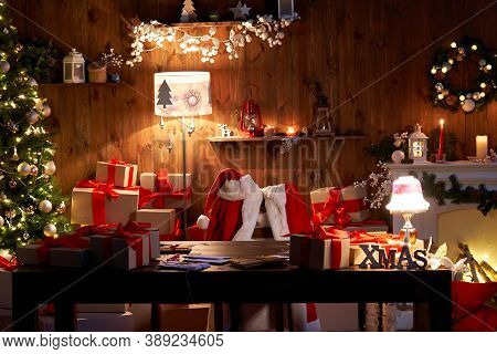 Santa Claus Costume And Hat Hanging On Chair At Table With Merry Christmas Decor Gifts Presents On H
