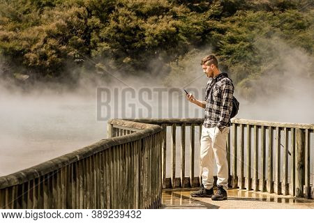 Man Looking At Mobile Phone While Touring On Place With Geothermal Activity.rotorua, New Zealand.