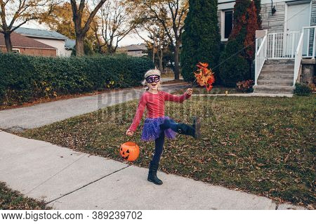 Trick Or Treat. Happy Child Girl With Red Pumpkin Basket Going To Trick Or Treat On Halloween Holida