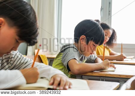 Asian School Children Sitting At Desk In School Writing In Note Book With Pencil, Studying, Educatio