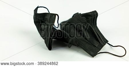 Used Surgical Mask Thrown On The White Floor. Mask Used For Covid 19 Protection Not Disposed Properl