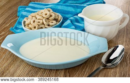 Small Oat Rings In Bowl On Striped Napkin, White Jug With Yogurt, Blue Oval Bowl With Yogurt, Metall