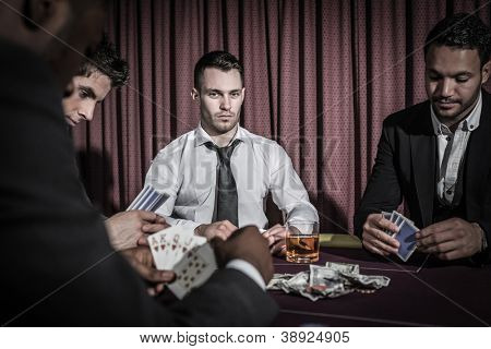 Serious man looking up from high stakes poker game in casino