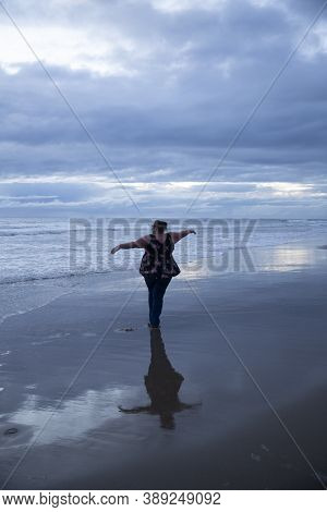 Woman Pirouettes Gracefully On The Beach After Sunset. Light Still Showing From Between Clouds. Refl