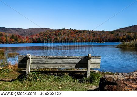 Wooden bench with colored autumn mountains and lake